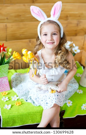 Happy girl with easter bunny ears celebrates easter emotionally - stock photo