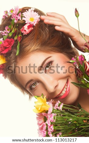 Happy girl with flowers in her hair and in her hands