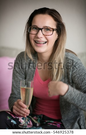 Happy girl with glasses and teeth braces, young cute caucasian champagne glass