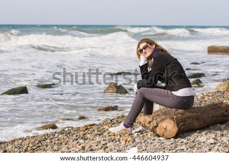 Happy girl with glasses sitting on a log on a rocky beach ocean