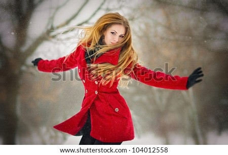 Happy girl with  gloves playing with snow and jump  in the winter landscape - stock photo