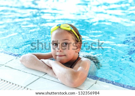 Happy girl with goggles relaxing in swimming pool