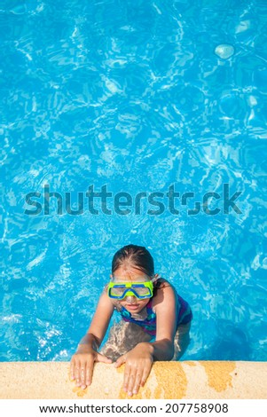 Happy girl with goggles relaxing in swimming pool - stock photo