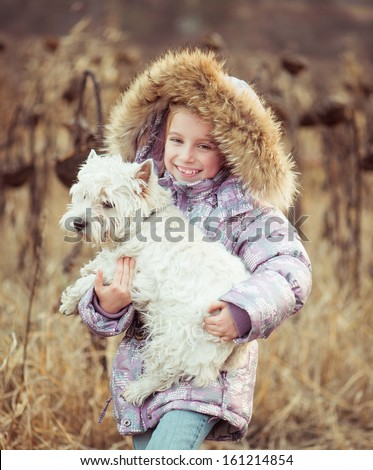 happy girl with her dog  in a field in autumn - stock photo