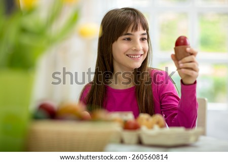 Happy girl with her Easter egg, holding and looking it  - stock photo