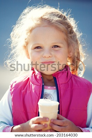 Happy girl with ice cream in summer day - stock photo