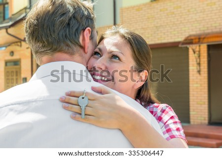 happy girl with key in hand, hugging her husband