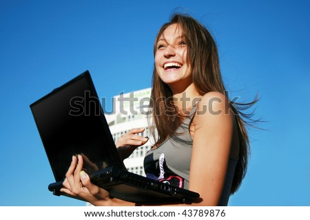 Happy girl with laptop near the building