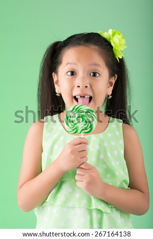 Happy girl with lost milk teeth eating lollipop - stock photo