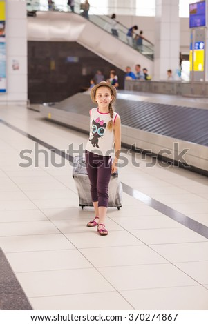Happy girl with luggage inside airport going on vacations trip