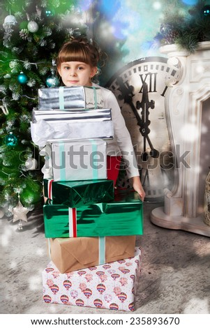 Happy girl with many presents while Christmas time - stock photo