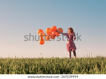 happy girl with orange balloons outdoor - stock photo