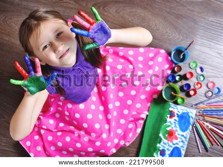 Happy girl with painted hands. Top view of little girl draws paints. - stock photo
