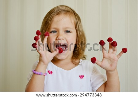 happy girl with raspberry on her fingers - stock photo