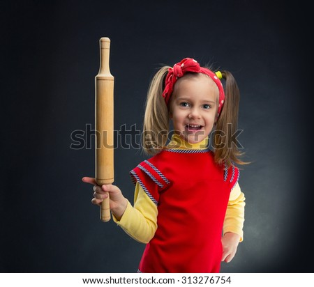 Happy girl with rolling-pin - stock photo