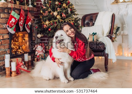 Happy girl with samoyed husky dog in Christmas decorations