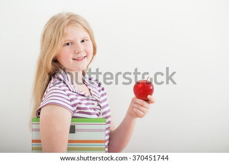 happy girl with scales and apple - stock photo