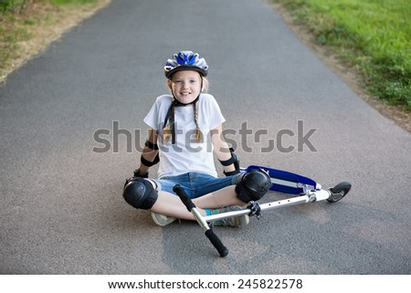 Happy girl with scooter, helmet and protection resting on the road, in the park, summertime - stock photo