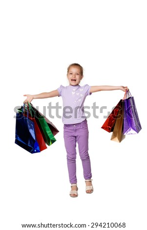 Happy girl with shopping bags standing at studio, isolated on white background - stock photo