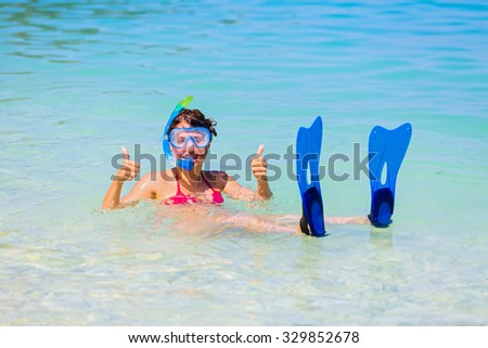 Happy girl with snorkeling gear and fins showing thumbs-up in the Mediterranean sea. - stock photo