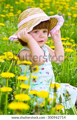 Happy girl with straw hat on the flower meadow - stock photo