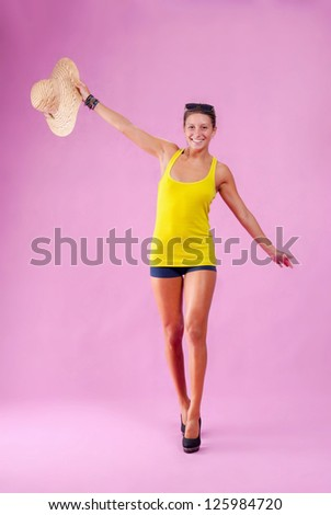 Happy girl with sunglasses and a straw hat on pink background