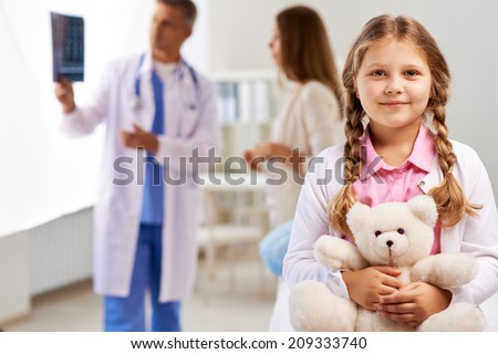 Happy girl with teddy bear looking at camera on background of doctor showing x-ray results to her mother - stock photo