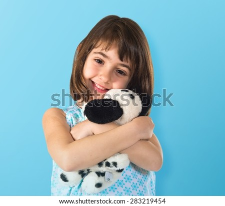Happy girl with teddy over colorful background - stock photo