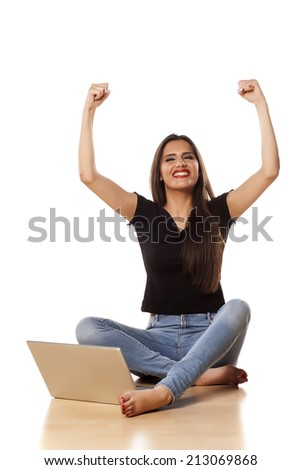 happy girl with the winning gesture sit on the floor and working on laptop