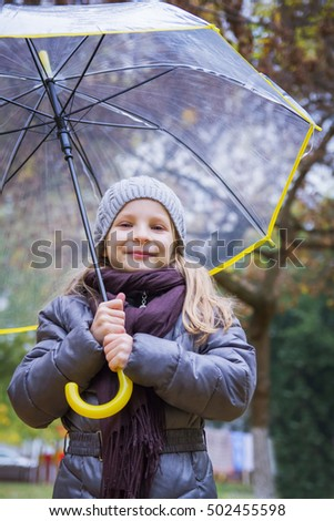 Happy girl with umbrella in autumn