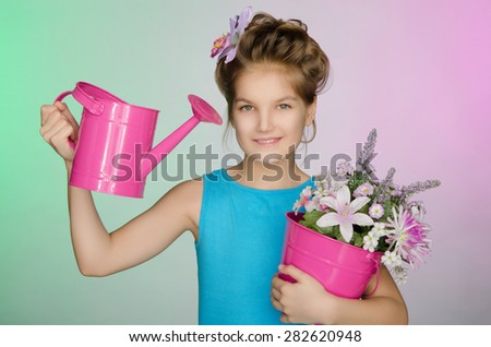 Happy girl with watering can and beautiful flowers on colored background - stock photo