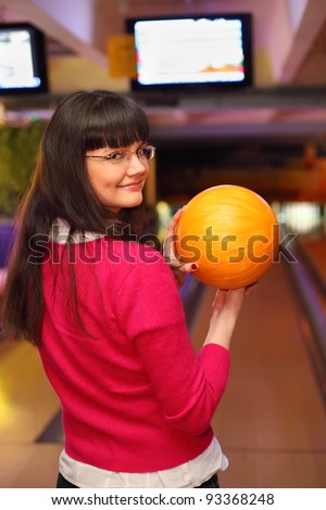 happy girl with yellow ball stands back to camera in bowling club and preparing to throw