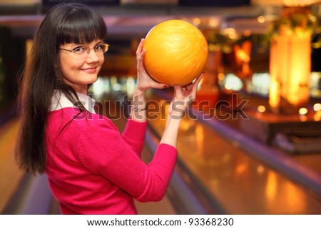 happy girl with yellow ball stands in bowling club and preparing to throw - stock photo