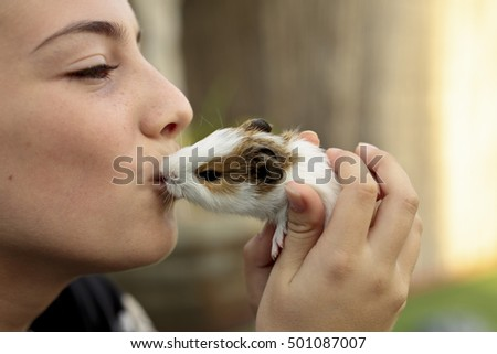 Happy girl with your Guinea pig in the hands, giving kisses. Horizontal capture.
