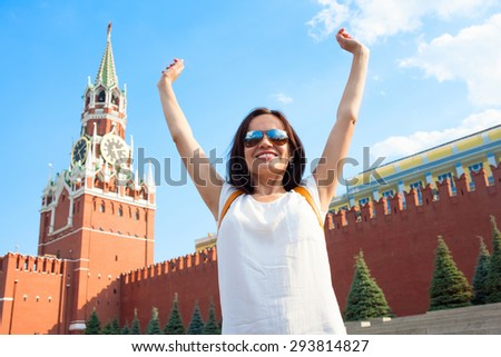 Happy girl woman tourist in sunglasses with raised hands on background of Red Wall of Moscow Kremlin and Spasskaya Tower. Focus on girls face and hairs