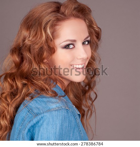 Happy girl 20-22 year old wearing casual denim shirt, posing over grey. Looking at camera. Young adults. Cheerful. Happiness.  - stock photo