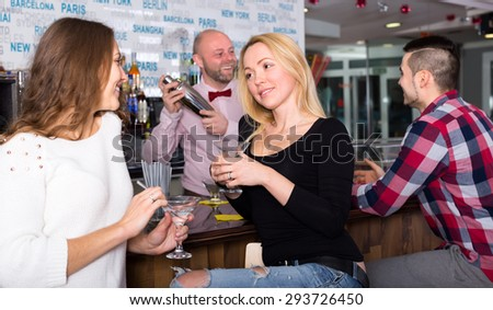 Happy girlfriends are having a conversation at a bar while barman is mixing a cocktail in a shacker for a man on the background