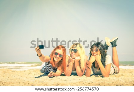 Happy girlfriends taking a selfie at beach - Concept of friendship and fun in the summer with new trends and technology - Best friends enjoying moments with modern smartphone - Vintage filtered look - stock photo