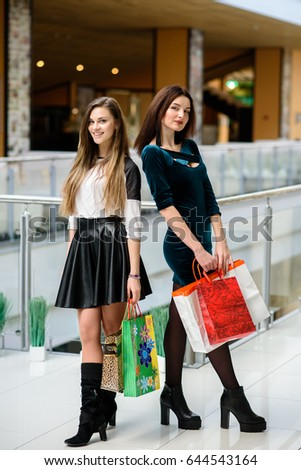 Happy Girls Are Shopping At The Mall