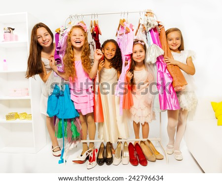 Happy girls during shopping choosing clothes - stock photo