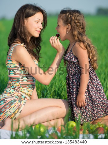 Happy girls eating cherry on green grass at spring or summer park picnic - stock photo