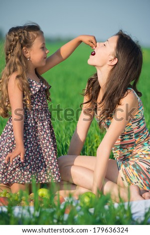 Happy girls eating cherry on green grass at spring or summer park picnic