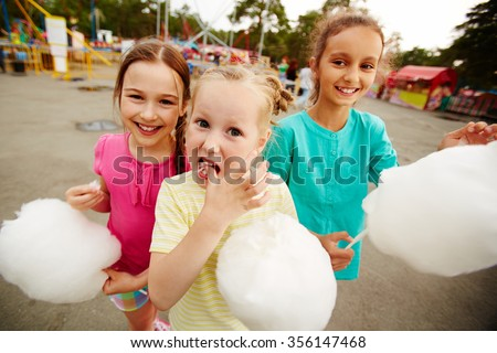Happy girls eating cotton candy in the park - stock photo
