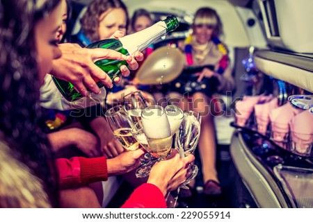 Happy girls having fun in limo, drinking champagne, hen-party - stock photo