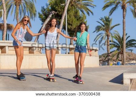 happy girls having fun on skateboards on holiday in Magalluf Mallorca - stock photo