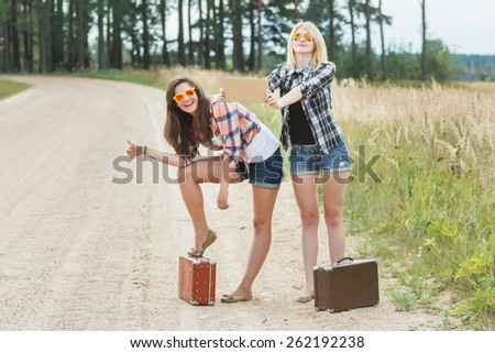 Happy girls hitchhiking with cardboard on country road - stock photo