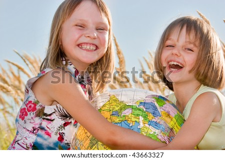 Happy girls holding big globe - stock photo