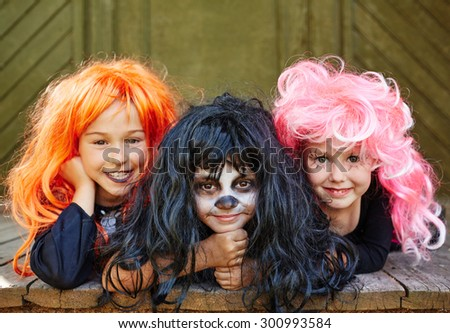 Happy girls in bright wigs looking at camera on Halloween day - stock photo