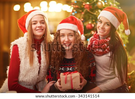 Happy girls in Santa caps looking at camera on Christmas evening - stock photo