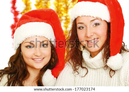 Happy girls in santa hats ,isolated on christmas decoration - stock photo